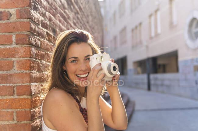 Молода жінка спирається на цегляну стіну за допомогою камери. — стокове фото