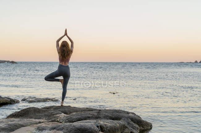 Молодая женщина практикует йогу на пляже, позируя на дереве, во время заката в спокойном пляже, Коста Брава, Испания — стоковое фото