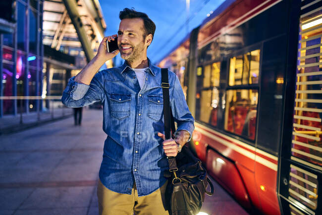 Man talking on phone in the city during evening with tram riding in background — Stock Photo