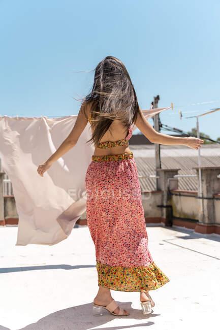 Позаду жінки, одягнена в модний топ і спідниця танцюють на даху. — стокове фото