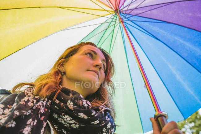 Jovem mulher sob guarda-chuva colorido — Fotografia de Stock