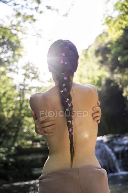 Вид сзади на голую молодую женщину, стоящую у водопада, Гарротха, Испания — стоковое фото