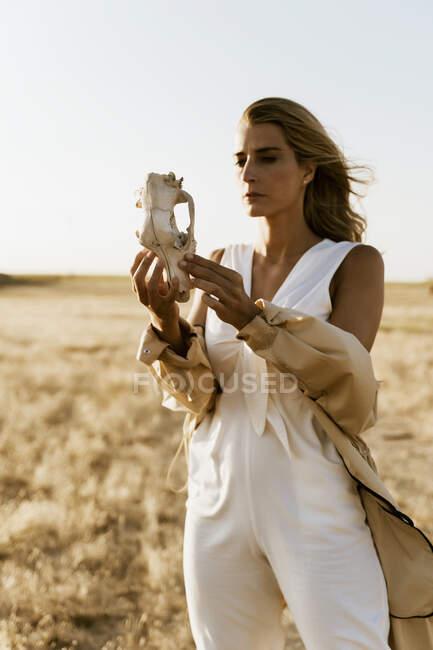 Жінка - мандрівник дивиться на череп. — стокове фото