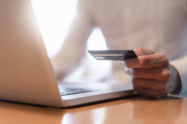 Man's hands holding credit card and while making an online payment with laptop, close-up — Stock Photo