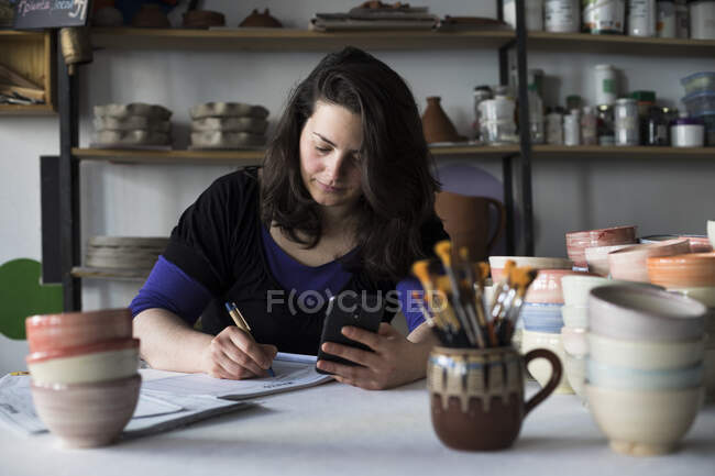 Potter doing accounting in her workshop — Stock Photo