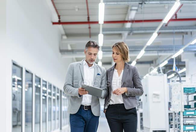 Empresaria y hombre de negocios con tableta caminando y hablando en una fábrica moderna - foto de stock