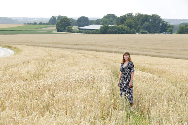 Усміхнена молода жінка в одязі з квітковим дизайном стоїть на полі. — стокове фото