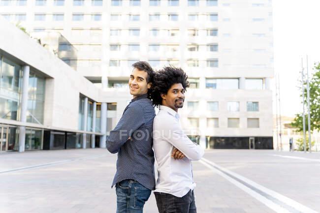 Retrato de dos empresarios confiados de espaldas a espalda en la ciudad, Barcelona, España - foto de stock