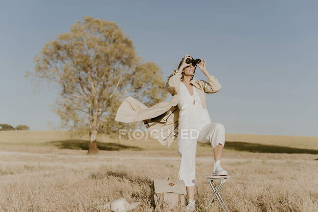 Female traveller looking through binoculars — Stock Photo