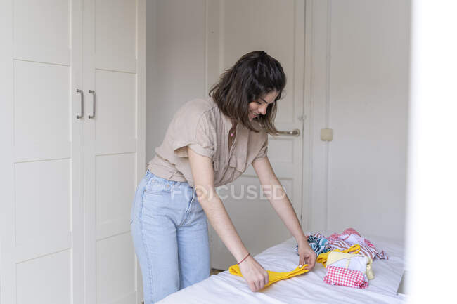 Young woman placing clothes on bed — Stock Photo