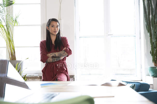Portrait of confident woman at the window in office — Stock Photo