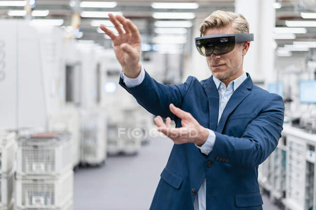 Businessman wearing AR glasses in a modern factory — Stock Photo