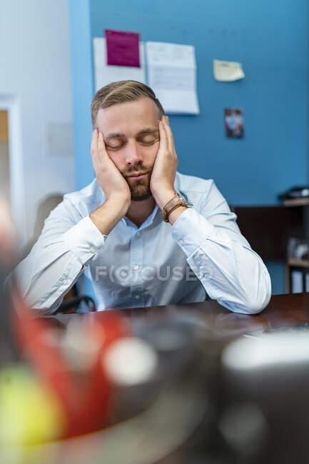 Hombre de negocios cansado con los ojos cerrados apoyados en el escritorio en la oficina - foto de stock
