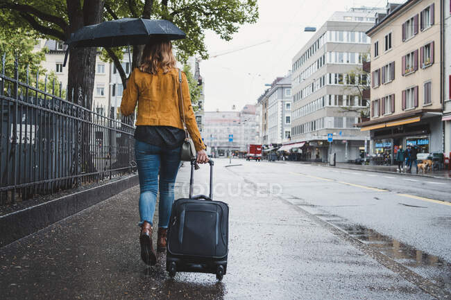 Young woman walking in the city on a rainy day, Zurich, Switzerland — Stock Photo