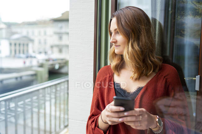 Young woman using cell phone at the balcony door — Stock Photo