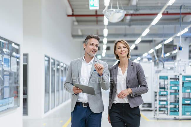 Femme d'affaires et homme d'affaires avec tablette marche et parler dans une usine moderne — Photo de stock