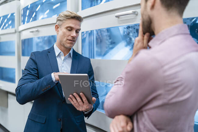 Two businessmen with tablet talking at machine in a modern factory — Stock Photo