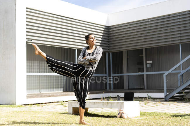 Female ballet dancer lifting her leg in front of an office building — Stock Photo