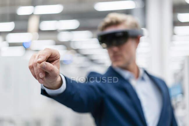 Homme d'affaires portant des lunettes AR dans une usine moderne — Photo de stock
