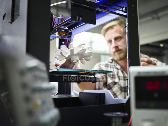 Техник с турбинным колесом печатается в 3D принтере — стоковое фото