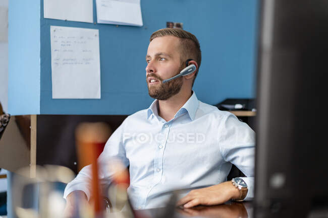 Businessman with headset at desk in office — Stock Photo