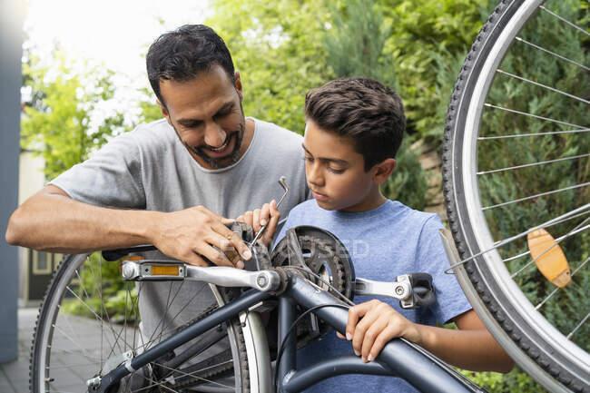 Батько і син разом ремонтують велосипед. — стокове фото