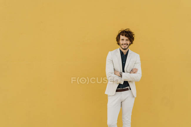 Portrait of smiling businessman in front of yellow wall — Stock Photo
