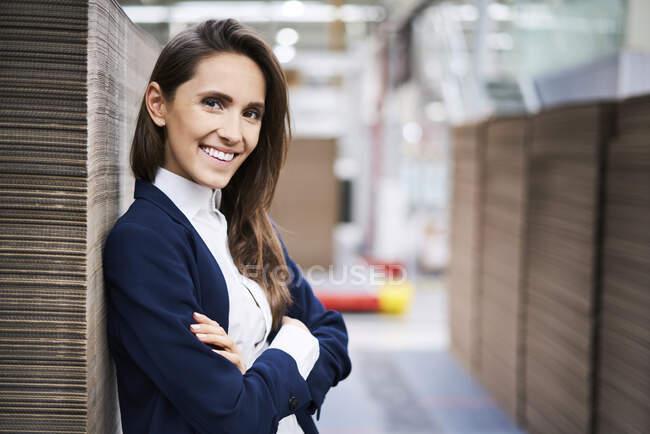 Portrait of smiling businesswoman in factory warehouse - foto de stock
