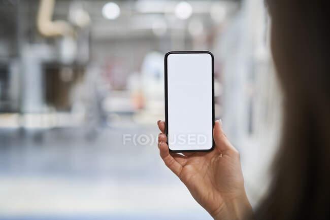 Primer plano de la empresaria que sostiene el teléfono celular en fábrica - foto de stock