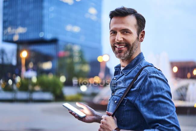 Retrato del hombre sonriente de pie en la ciudad durante la noche y usando un teléfono inteligente - foto de stock