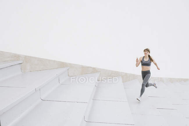 Young woman in sportswear running on concrete bleachers and listening music on a smartphone — Stock Photo