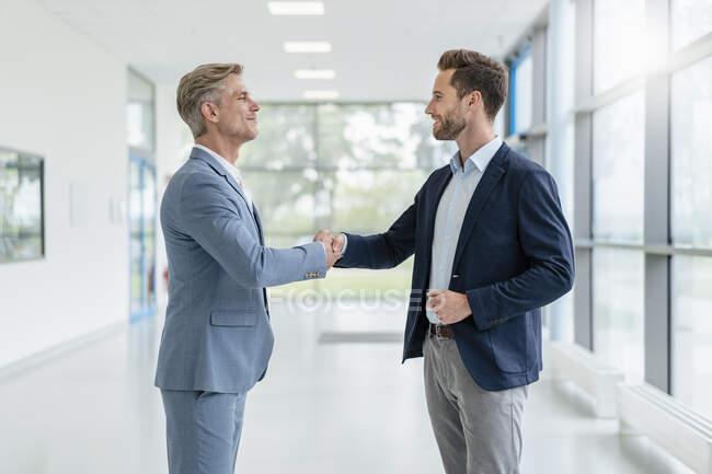 Два бізнесмени, які потиснули руки на проході. — стокове фото