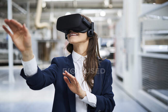 Businesswoman wearing VR glasses in factory — Stock Photo