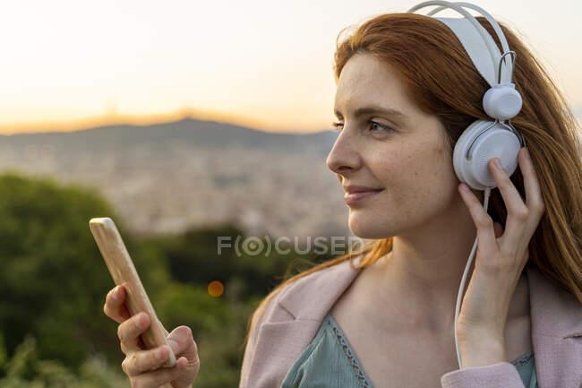 Mujer pelirroja joven con auriculares y teléfono inteligente en el punto de vista - foto de stock