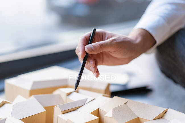 Close-up of man with pencil pointing at architectural model in office — Stock Photo