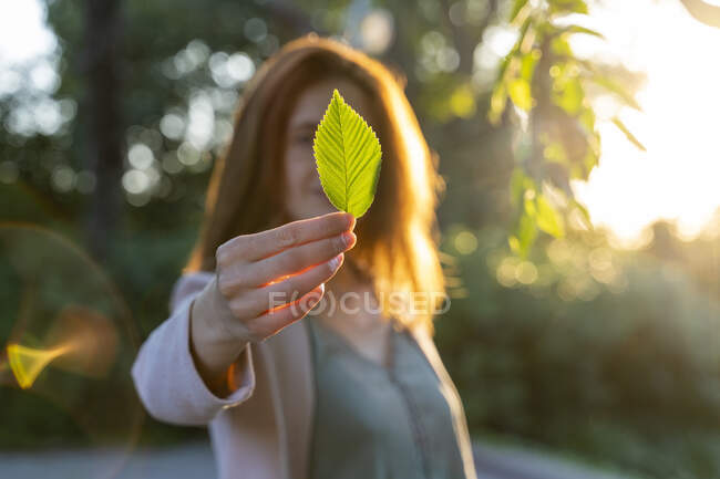Young redheaded woman holding green leaf in a park — Stock Photo