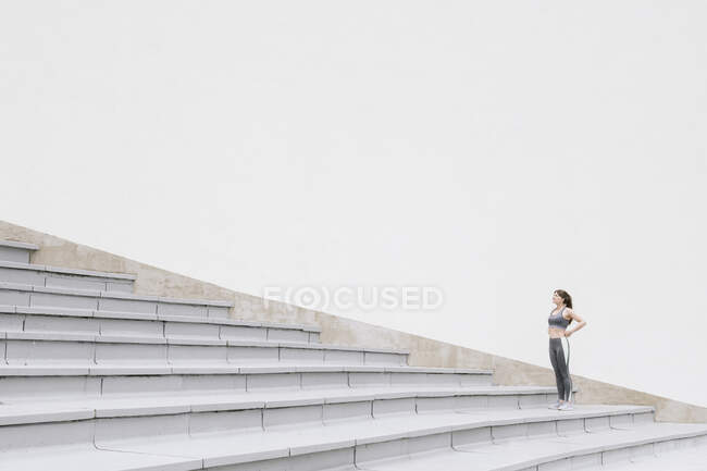 Sportswoman standing and looking up on concrete bleachers — Stock Photo