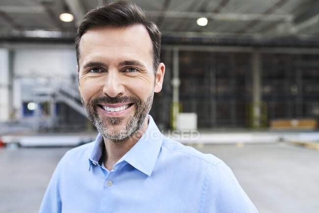 Portrait of smiling businessman in a factory — Stock Photo