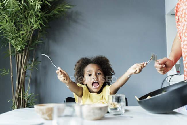 Портрет радісної дівчинки з мамою за обіднім столом. — стокове фото
