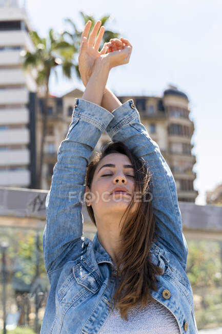 Young woman with arms raised and closed eyes — Stock Photo