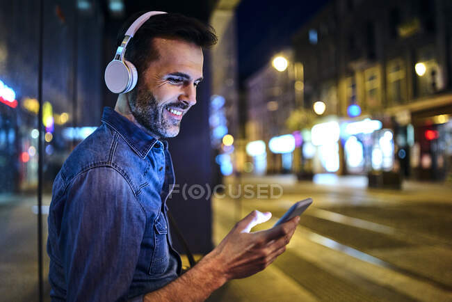 Smiling man with headphones using smartphone while waiting for night bus in the city — Stock Photo