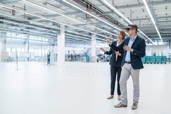 Homme d'affaires avec lunettes AR et femme d'affaires dans un hall d'usine — Photo de stock