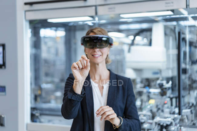 Businesswoman wearing AR glasses in a modern factory — Stock Photo