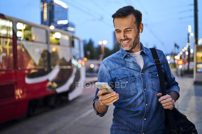 Hombre usando el teléfono inteligente y escuchar música mientras está de pie en la parada de tranvía por la noche - foto de stock
