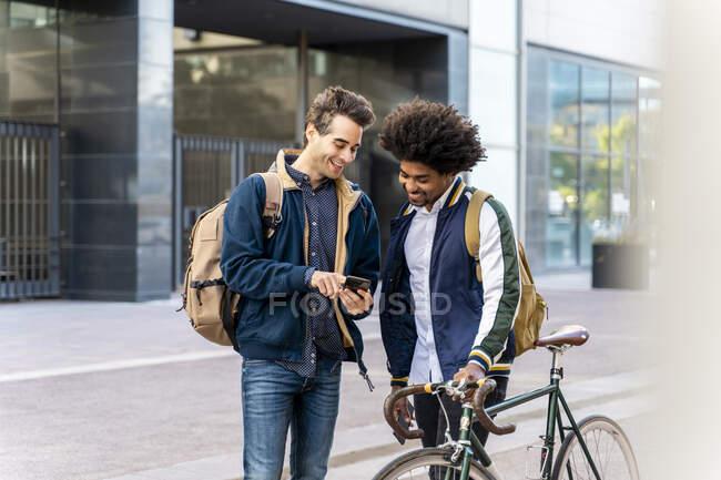 Dois empresários casuais felizes com reunião de telefone celular na cidade, Barcelona, Espanha — Fotografia de Stock