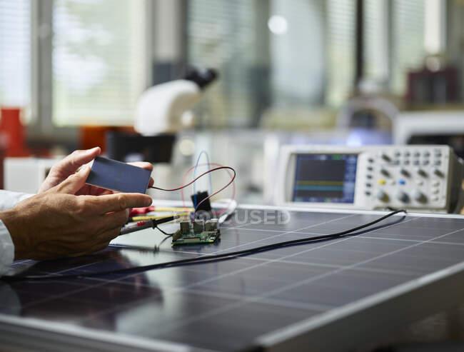 Техник держит кремниевый солнечный элемент на солнечной панели — стоковое фото