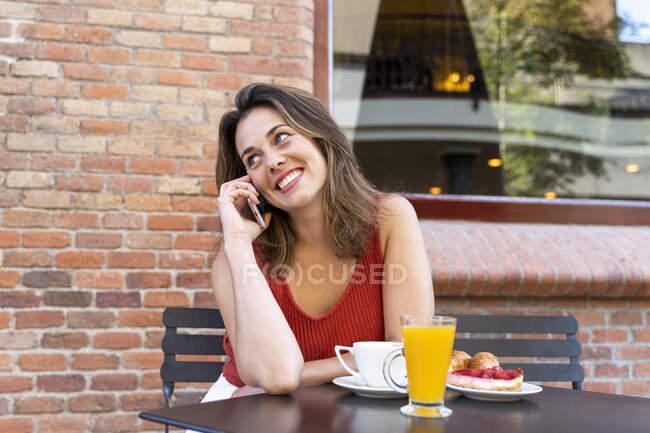 Retrato de jovem sorridente ao telefone sentado no café da rua — Fotografia de Stock
