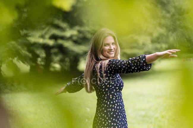 Sorridente giovane donna nel parco — Foto stock