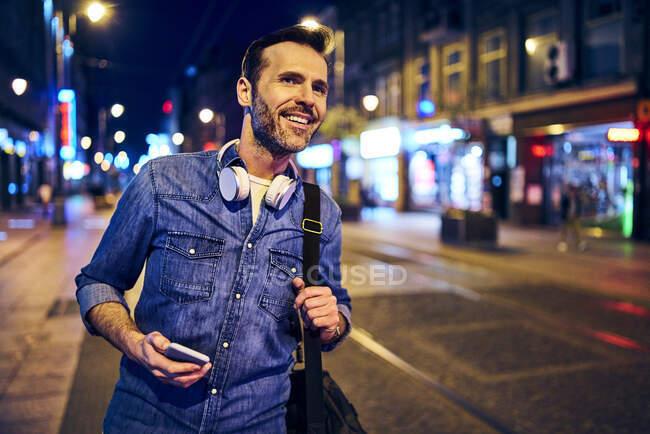 Вночі, чекаючи трамвая, ви посміхаєтесь зі смартфона. — стокове фото