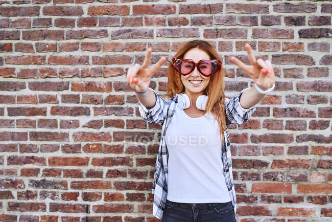 Cheerful young woman in heart-shaped glasses making peace gestures and smiling at camera — Stock Photo
